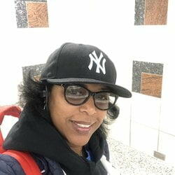 A woman in a black New York Yankees Hat